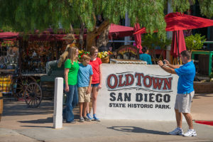 Family having picture taken next to Old Town San Diego State Historic Park sign